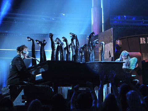 """After jumping into a stage furnace, Gaga emerged to sing a duet with Elton John from a double-sided piano with charred hands sticking out. Both covered in soot and wearing matching sequined sunglasses, Elton and Gaga sang a medley of her """"Speechless"""" and his """"Your Song."""" Elton even changed his lyric to sing, """"How wonderful life is with Gaga in the world."""""""