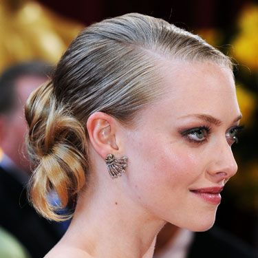 Rocking a deep side part and neat, low chignon, the <i>Dear John</i> actress kept the focus on her flawless face.