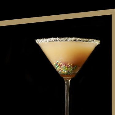 """<p>2 oz. vodka<br />2 oz. white peach puree <br />1 oz. ginger-infused simple syrup <br />½ oz. lemon juice<br />Silver and pink sanding sugar (for rim) <br />Silver sugar beads</p><p>To make the peach puree, peel a peach and put it in a blender for about 10-15 seconds. To make the ginger syrup, bring half a cup of water and half a cup of sugar to a boil in a small saucepan. Throw in some fresh chopped ginger. Reduce, and stir until the mixture thickens. Strain out the ginger and let the syrup cool to room temperature Now, in a mixing glass, combine the peach puree, the ginger syrup, the lemon juice and the vodka&#x3B; shake. Strain into a martini glass rimmed with the sanding sugar. (If you can't find sanding sugar in the baking aisle of your supermarket, substitute a small candy, like Nerds, crushed into powder.) Drop the silver sugar beads in the bottom of the glass for more """"bling.""""</p>"""