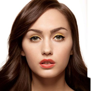 """<p>Layering canary yellow and black eye liner makes a huge impact, says NYC makeup artist Susan Giordano. Create the black cat's-eye shape with liquid liner. Once it's dry, use a pointy liner brush to apply a yellow cream shadow  """"Keep it flush against the black, and do two coats,"""" says Giordano. Tint the inner corners of the lower lash lines with a subtler but complementary gold liner, apply a light coat of mascara (lashes shouldn't overpower lids), and amp up lips with an orange-red gloss.</p><p>See the next slide for a list of products we suggest for this look.</p>"""