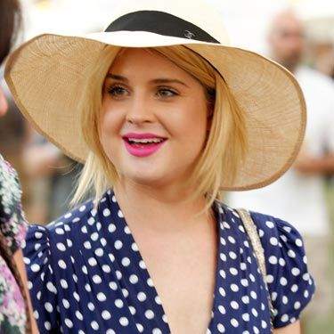 "Kelly's wide-brim hat frames her face and blocks out plenty of <a href=""http://www.cosmopolitan.com/advice/sun-safe/practice-safe-sun"">sun</a>. Plus, it looks great with her retro, polka-dot dress and on-trend <a href=""http://www.cosmopolitan.com/hairstyles-beauty/beauty-blog/emma-stone-lipstick-041311"">hot pink lipstick</a>."