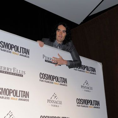 How does FFM of the Year Russell Brand make an entrance? By scaling the huge sign behind the red carpet and poking his head out, of course.