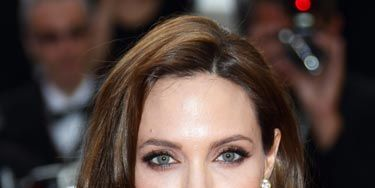 """Angelina Jolie's sexy look is all about smoky eyes in rich shades of brown. Use a palette of different hues, like <a href=""""http://www.drugstore.com/rimmel-glam-eyes-quad-eye-shadow-palette-smokey-brun-002/qxp345250""""target=""""_blank"""">Rimmel Glam Eyes Quad</a>, focusing the darkest color around your lashline and blending outward."""