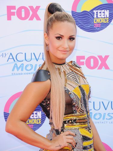 "<p>Demi Lovato's ponytail is reaching new heights, thanks to the leather strap that's wrapped around her hair. We love that her edgy hair style matches her outfit 100 percent.</p> <p><strong>At-Home Tip:</strong> If you want your ponytail to be as long as Demi's, pick up a hair extension to give you some length. After you <a title=""hair extensions"" href=""http://www.cosmopolitan.com/hairstyles-beauty/hair-care/how-to-wear-hair-extensions#slide-3"" target=""_blank"">apply it to your head</a>, pull your hair up into a high ponytail at the crown of your head and secure it with a hair tie.</p> <p>Then, take a structured fabric, like leather, and wrap it around the elastic band and over the hair that's coming out of the ponytail, and then back toward the hair tie. You'll want to pin it as close to the band as possible to keep it from unwinding.</p>"