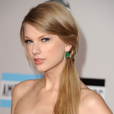 Taylor Swift has major bangs, but they can still be pulled to the side and hidden in a pony. If you look closely, you can tell that her tresses are loosely braided to help hold them in place.