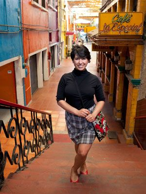 """<p>A trendy skull and rose print bag instantly amps up a mock-neck top and plaid skirt getup. Glenda Canizales, owner of Mua Cafe, a coffee shop, boutique, and performance space,located on Pasaje Gomez in Tijuana.</p> <p> </p> <p>Alicia Santistevan, photographer,<a href=""""http://www.aliciasantistevan.com/"""" target=""""_blank""""> AliciaSantistevan.com </a></p>"""