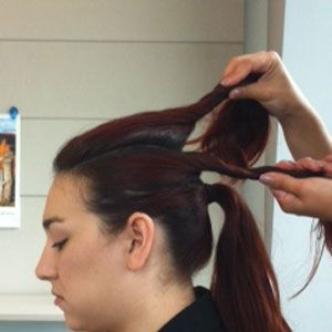 <p>Part your hair into three sections as shown. Brush the bottom section into a ponytail.</p>