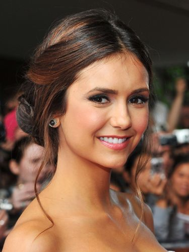 Twists, tendrils, and braids: There's a lot going on with Nina Dobrev's 'do&#151;and we like it! Oh, and don't worry, it only <i>looks</i> complicated.<br /><br /> <b>Make it your own:</b> Section off your bang area from ear to ear and clip. Gather the rest of your hair into a low, loose ponytail. Unclip the front section and create a center part. Then, twist the hair on each side of the part and gather into one pony that sits right on top of the first ponytail. Combining the hair from both ponys, create two-to-three braids. Twist the braids into one bun; pin to secure. <br /><br /> Finally, use your fingers to gently widen each braid and pin them together, so you don't see any gaps. Pull out a few soft tendrils and spritz your hair with a light hold hairspray. Try Suave Professionals Touchable Finish Hairspray, $3.75, drugstores.com.