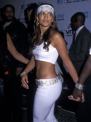 """<p>Our favorite Puerto Rican from the block always turns head with her fashion choices from super low cut dresses to laid back city girl looks like this one.</p> <p> </p> <p>Get the look:</p> <p>White Pants, <a href=""""http://www.moda.com/moleton_pants/index.shtml"""" target=""""_blank"""">Moda.com</a></p> <p>Bandana, <a href=""""http://www.etsy.com/listing/85186058/jeweled-bandana-white-heavily-0blinged?utm_source=googleproduct&utm_medium=syndication&utm_campaign=GPS&gclid=CIe_mdHr8bICFQWe4AodNEAAHg"""" target=""""_blank"""">Etsy.com</a></p> <p>Cropped topm, <a href=""""http://us.asos.com/ASOS-00-s-Crop-Top/x8cs1/?iid=1916670&cid=4169&sh=0&pge=2&pgesize=200&sort=-1&clr=White+green&utm_source=google_product_search&utm_medium=organic&utm_campaign=google_product_search&WT.tsrc=Google%20Product%20Search&r=2&mporgp=L0FTT1MvQVNPUy05MHMtQ3JvcC1Ub3AvUHJvZC8"""" target=""""_blank"""">Asos</a></p> <p> </p>"""