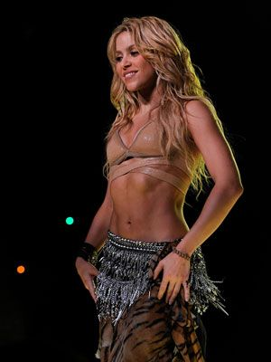 """<p>The hip shaking Colombiana always hits the stage with glamorous belly dancing attire. Pair a belly dancing top and scarf with plain leggings, and keep your hair kinky and wild to get Shak's signature natural-but-sexy-look.</p> <p> </p> <p>Get the look:</p> <p>Belly dancing scarf, <a href=""""http://www.amazon.com/Black-Belly-Dancing-Scarf-Silver/dp/B004AYJ12A/ref=sr_1_9?ie=UTF8&qid=1349730364&sr=8-9&keywords=Belly+Dancing+Skirts"""" target=""""_blank"""">Amazon.com</a></p> <p>Leggings, <a href=""""http://www.forever21.com/Product/Product.aspx?BR=f21&Category=btms_leggings&ProductID=2017306226&VariantID="""" target=""""_blank"""">Forever21.com</a></p> <p>Top, <a href=""""http://www.etsy.com/listing/110943481/silver-metallic-tube-top-bikini-bra-top"""" target=""""_blank"""">Etsy.com</a></p>"""