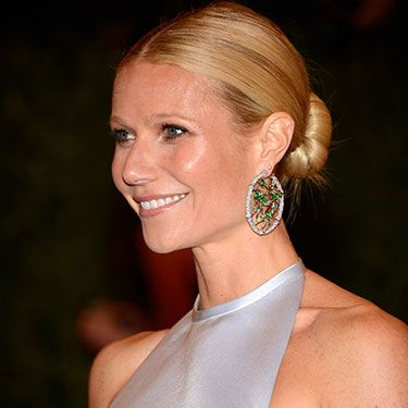 We don't know if its the sleekness, the sharp center part, or the few sexy escaped tendrils that make Gwyneth Paltrow's bun both festive and timeless—but it <i>so</i> is. Amp up the party quotient with a sparkly statement earring!