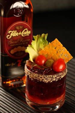 1 ounce Flor de Cana 7 yr rum 2 muddled Roma tomatoes 1 ounce iceberg lettuce water* 1 ounce beef (well reduced) 2 tbsp toasted bread crumbs 1 tsp dry mustard powder 2 tbsp aged cheddar 1 large Kosher dill pickle Salt and pepper to taste  Heat pan to medium, sprinkle in cheddar, and use the sides of a spoon to gather cheese into a circle. Brown and remove from pan to cool on a plate. Mix breadcrumbs with dry mustard and wet the rim of a glass with pickle juice and dip in crumb mixture.  Muddle tomatoes and ice and slowly pour lettuce water*. Stir rum and beef juice together in a shaker and float over ice.  Sprinkle with salt and pepper and garnish with cheddar and a pickle knot.  *To make lettuce water, put a wedge of lettuce through a juicer or food processor and liquify.