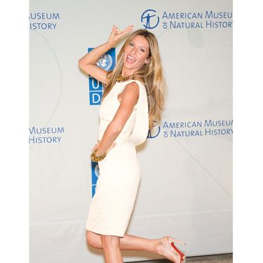 "Brazilian supermodel Gisele Bundchen is usually playful on the red carpet. In this pose, her right hand is raised above her head—when we gesture above the shoulders and head we are telling the world ""I'm powerful and want to be seen."" Her inviting smile non-verbally says that she's open to getting to know new people."