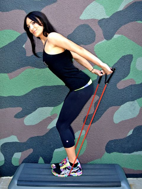 "<p>Stand on the middle of a resistance band, grab a handle in each hand, and <a href=""http://www.cosmopolitan.com/sex-love/positions/the-lusty-lean-sex-position?click=main_sr"" target=""_blank"">lean forward at the hips</a>. Press your arms straight back as high as you can, keeping your back flat and knees slightly bent. Next, bend your elbows, bringing your hands up to your shoulders, and then extend back again. Do three sets of 15 reps.</p>"