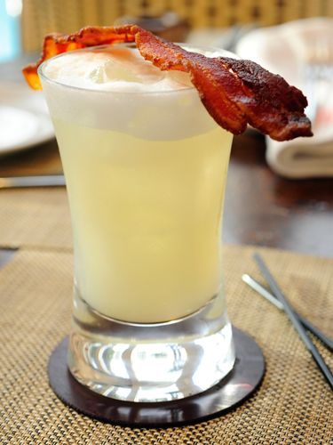 """<i>1½ oz. bacon infused gin<br />1 oz. egg whites<br />½ oz. fresh lemon juice<br />½ oz. honey syrup<br /><br /></i>To infuse gin, place bacon pieces into bottle of alcohol and let it sit in the fridge over night. To make honey syrup, mix equal parts hot water, sugar, and honey until sugar is dissolved. Combine all ingredients in a cocktail shaker filled with ice. Shake vigorously and strain into a glass.<br /><br /><i>Source: <a href=""""http://www.figsantamonica.com/"""" target=""""_blank"""">FIG Restaurant</a></i>"""