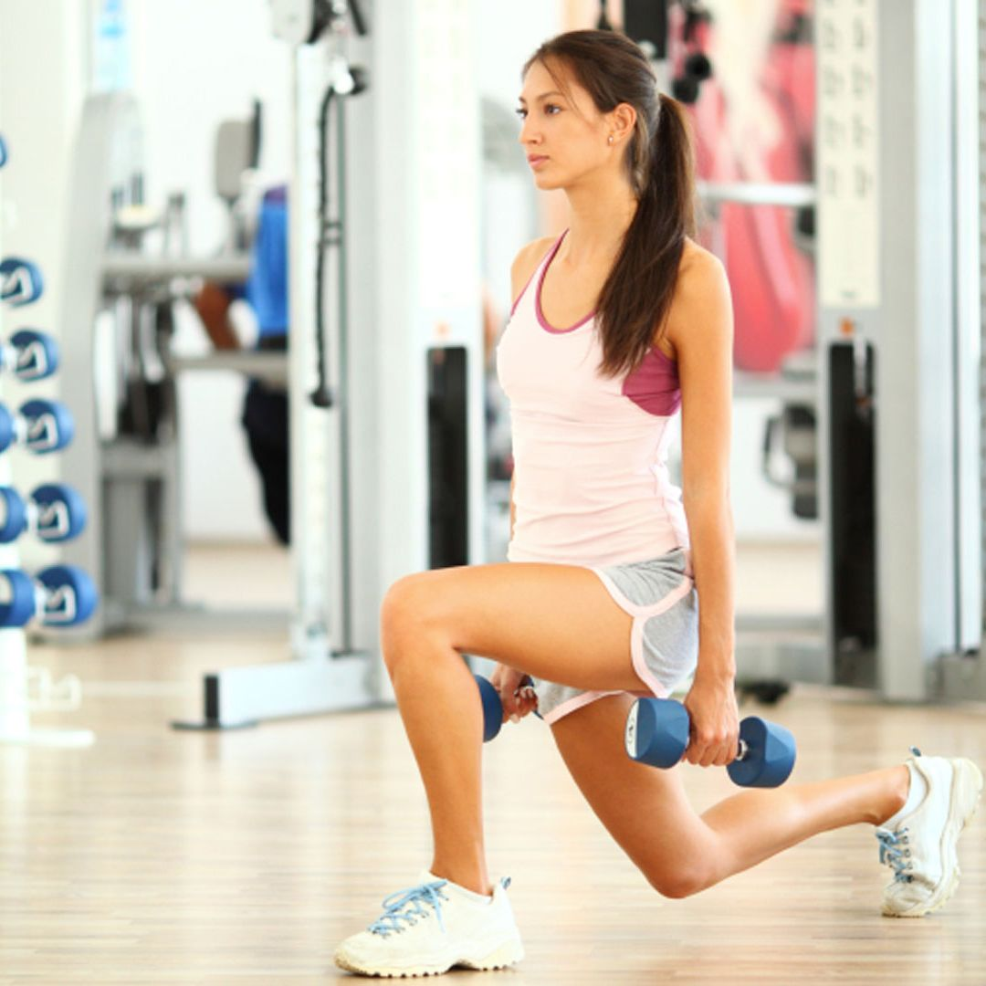 "<p>Stand with your feet hip width apart and chest up. Hold dumbbells* at your sides, palms facing in. Step back with your right leg, and when it hits the ground, <a href=""http://www.cosmopolitan.com/advice/health/butt-toning-exercise?click=main_sr"" target=""_blank"">squeeze your glutes</a> and descend into a lunge. Bend your front left leg while dropping your back knee almost to the ground. Return to starting position&#x3B; repeat with your left leg in back. Do four sets of six to eight lunges, alternating legs.</p>