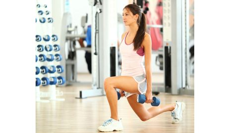 "<p>Stand with your feet hip width apart and chest up. Hold dumbbells* at your sides, palms facing in. Step back with your right leg, and when it hits the ground, <a href=""http://www.cosmopolitan.com/advice/health/butt-toning-exercise?click=main_sr"" target=""_blank"">squeeze your glutes</a> and descend into a lunge. Bend your front left leg while dropping your back knee almost to the ground. Return to starting position; repeat with your left leg in back. Do four sets of six to eight lunges, alternating legs.</p> <p>Targets: Glutes, Quads, Hamstrings & Adductors</p> <p>Choose a dumbbell weight that makes you feel challenged (around 10-25-pounds for most women). By the end of the set, you should feel that you could have only gotten out one or two more quality reps.</p>"