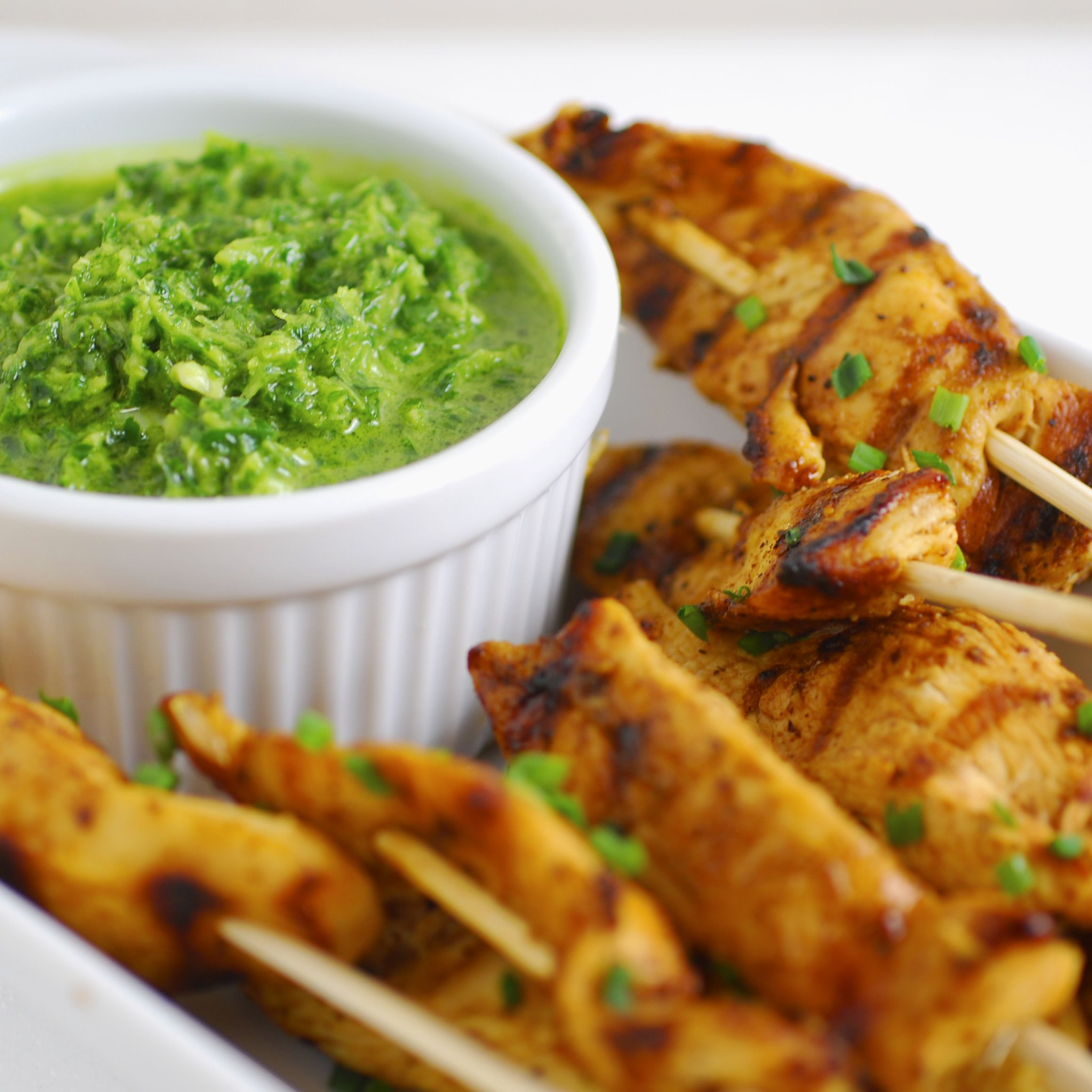 <p>Who doesn't love food on a stick? These chicken skewers are sure to be a hit. Chef Alejandra Ramos featured this delicious recipe in our Spring 2013 issue. The <em>chimichurri</em> sauce is an amazing extra kick to a simple dish. </p><p><strong>Ingredients</strong></p><p>For the sauce</p><p>1/2 bunch fresh parsley, stems removed</p><p>1/2 bunch fresh cilantro, stems removed</p><p>4 garlic cloves</p><p>1/2 cup olive oil</p><p>1/2 cup red wine vinegar</p><p>1 teaspoon kosher salt</p><p>For the chicken</p><p>1 pound chicken tenders</p><p>3 tablespoons olive oil</p><p>1 teaspoon kosher salt</p><p>1 teaspoon ground black pepper</p><p>1 teaspoon ground cumin</p><p>Juice of 2 limes</p><p>Wooden skewers</p><p><strong>Preparation</strong></p><p>Make the sauce: combine all ingredients in a blender or food processor and process until coarsely chopped. Set aside.</p><p>Cut chicken tenders in half and toss in a bowl with olive oil, salt, black pepper, cumin, and lime juice. Heat a grill pan or skillet, and cook chicken 3-4 minutes on each side until cooked through and slightly charred. Once fully cooked, thread chicken onto skewers and serve with sauce on the side for dipping. </p>
