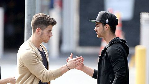 Cap, Sleeve, Baseball cap, Interaction, Gesture, Wrist, Conversation, Holding hands, Street fashion, Sweater,