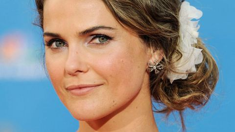 <p>Take a cue from <em>The Americans</em> star and tuck your loose curls into a chic side bun. Glam things up with a festive floral pin! Just the thing for a wedding date with him.</p>