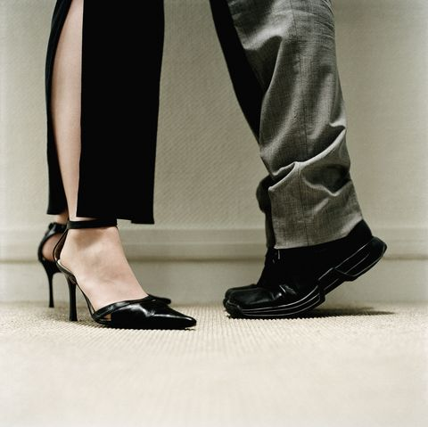 Man's feet on tiptoes standing in front of a woman's feet in heels