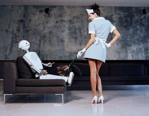 A woman dusting while a robot sits in a chair and drinks whisky
