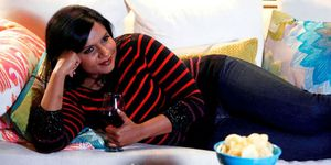 Mindy Kaling lying on the sofa with wine and crisps