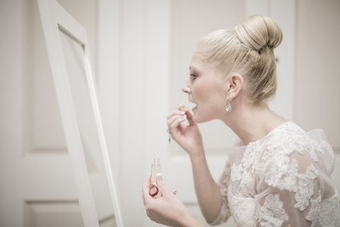 Bride applying make-up before wedding