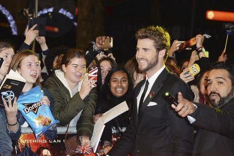 Girl holding doritos at the hunger games mockingjay London premiere as Liam Hemsworth walks past