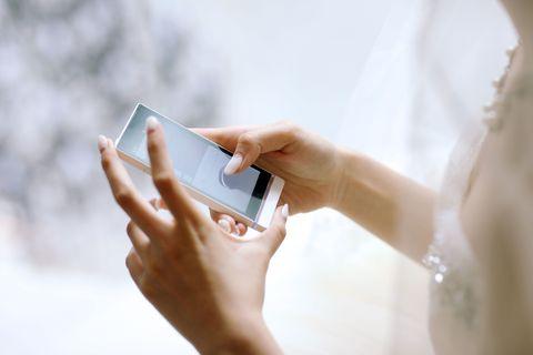 Bride texting at a wedding