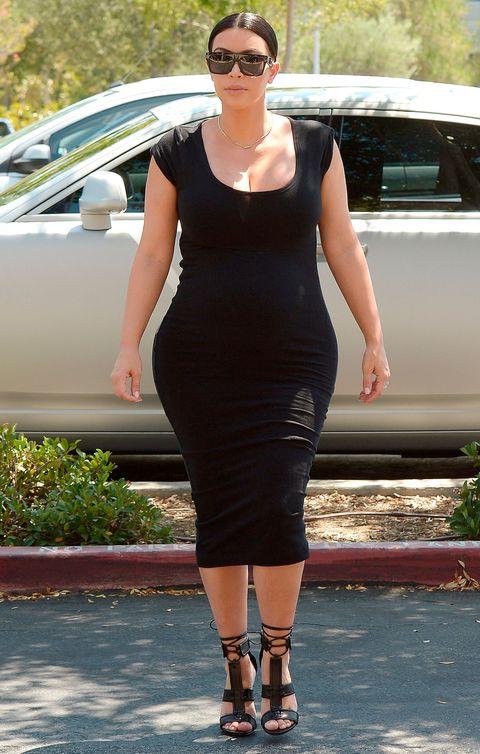 Kim Kardashian out and about wearing a black bodycon dress