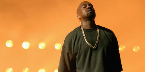 Kanye West performing onstage with his eyes closed in front of all of the lights