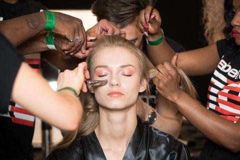 Model having makeup applied backstage