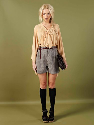 """<p>Look sweet and innocent in this peach sheer blouse and high-wasted plaid shorts. Add a satchel and your school girl cool!</p> <p>Harvey Blouse £20, Jeorgie shorts £18, <a href=""""http://www.boohoo.com/collections/70s-country-girl/icat/70scountrygirl/""""target=""""_blank"""">boohoo.com</a></p>"""