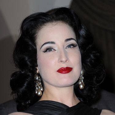 Whiter-than-white skin, jet black brows, lashings of liner and blood red lips. Dita Von Teese could have come straight from the set of a Dracula film.