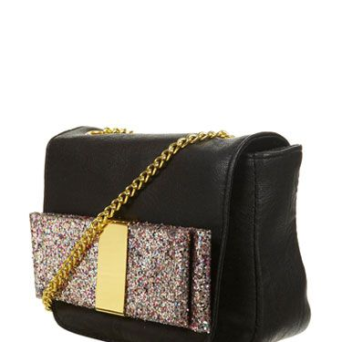 """<p>This gorgeous bag is ideal for the party girl in your group. While the classic black colour and hands-free across-body style is very practical, the frivolous, glittery bow panel just screams P-A-R-T-Y!</p> Handbag, £22, <a href=""""http://www.topshop.com/"""">Topshop</a>"""