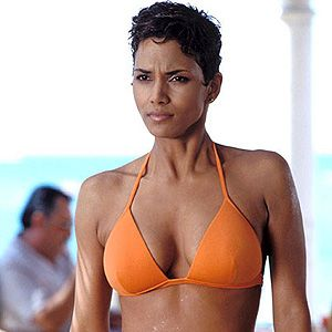 """<p>How can we forget Halle Berry emerging out of the water in that fabulous orange bikini as Jinx Johnson in Die Another Day? She heats things up with Pierce Brosnan as another sexed-up Bond girl!</p><p><strong>Top secret tip</strong>: <a href=""""http://www.boots.com/en/Black-and-White-Pluko-Hair-Dressing-Pomade-50ml_873139/?CAWELAID=334511675&cm_mmc=Shopping%20Engines-_-Google%20Base-_---_-div%20classeditContentAreaBlack%20and%20White%20Pluko%20Hair%20Dressing%20Pomade%2050mldiv"""" target=""""_blank"""">Black and White Pluko Hair Dressing Pomade</a> is the perfect weapon for sculpting shorter hair into this spikey style.</p>"""