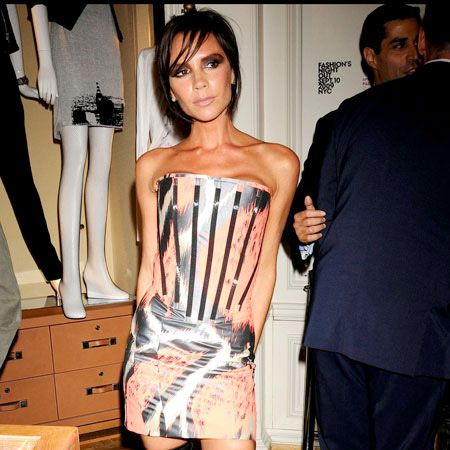 Victoria Beckham's tan almost clashed with her orange Giles Deacon dress as she posed provocatively at Fashion's Night Out held at Bergdorf Goodman in NYC. And Posh was looking super skinny in her knee-length boots but we definitely approve of the dramatic smokey eyes...  <br />