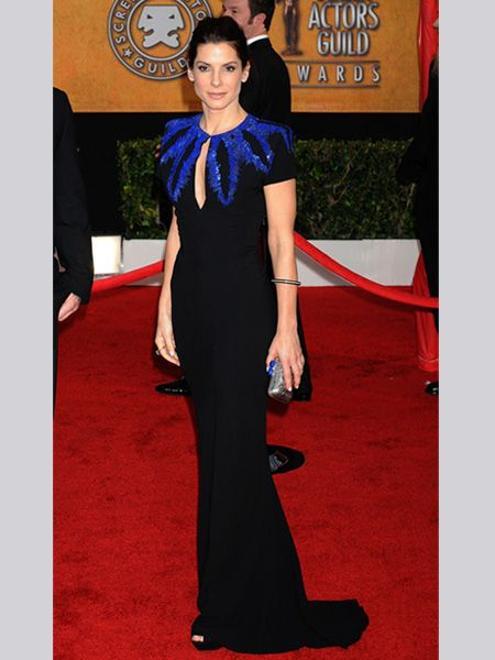 <p>Sandra looked super sophisticated in a black gown with blue sequin feather detailing by Alexander McQueen, accessorised with a chic silver box bag</p>