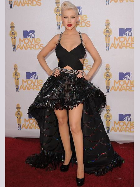<p>Christina sexed it up in a voluminous Versace dress with a trailing back and chain detailing </p>