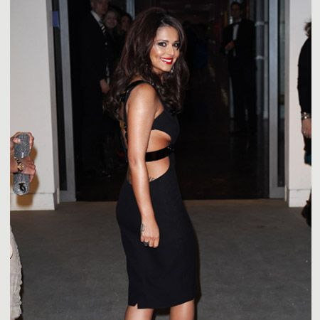 Showing off her body ink Cheryl Cole stepped out in a black Versace dress with bondage style strapping showing off her lower back tattoo. Accessorising with a pair of bright red Louboutins, matching lips and a huge smile, Cheryl and The X Factor won Most Popular Talent Show