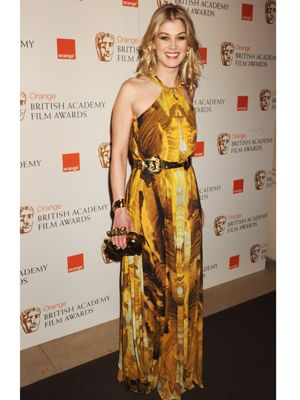 Rosamund Pike brightened up the rainy red carpet with her yellow printed halterneck gown by Alexander McQueen. Pulling her outfit in with a gold buckle belt and clutching a McQueen bag, we love Rosamund's sunny disposition