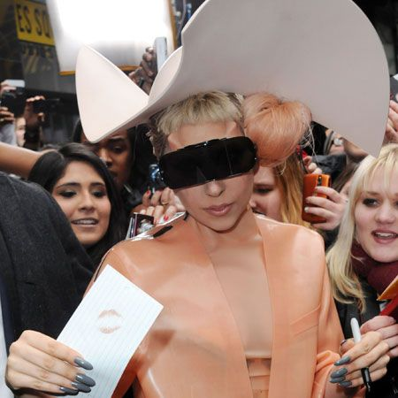 "Lady Gaga sported some interesting eyewear and a ""latex condom-inspired"" dress to promote AIDS awareness on Good Morning America."