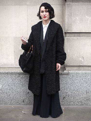 <p>Despite bold, bright colours being the go-to trend this season, this fashionista opted for a layered black look instead – and totally pulled it off. The pleated skirt, retro curls and red lips made this lady stand out from the crowd</p>