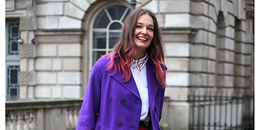 <p>Determined not to let a bit of rain spoil the fashion week fun, this lady wore dazzling colours to match her dip-dyed hair</p>