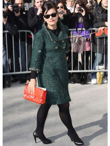 <p>Lily arrived at the Chanel show wearing a divine moss green tweed coat by the luxe label and carrying one of their tangerine coloured quilted shoulder bags which matched her stand-out lippy</p>