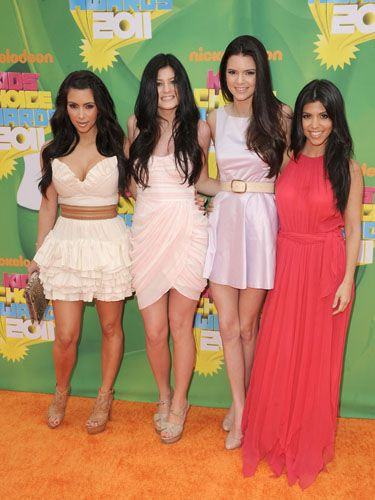<p>Kim, Kylie and Kendall went for short frocks in pale shades whilst Kourtney opted for a hot-hued maxi dress, and all wore their dark locks long and loose</p>