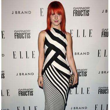<p>Hayley goes for a more mature look in this stripy monochrome dress at Elle's Women in Music event this year. We love her leopard print clutch</p>