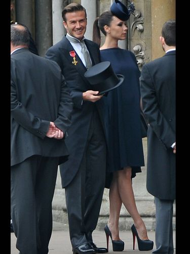 David Beckham looks dapper in Ralph Lauren, wearing his OBE on his lapel. Victoria's stunning hat is Philip Treacy, and her dress is one of her own design - modified for her growing baby bump.  Her matching platform shoes are custom-made Christian Louboutin. Gorgeous!