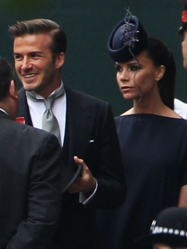 Here's a closer look at David's clean-cut look - and swoonworthy smile - and Victoria's spectacular inky Philip Treacy hat. She has her hair in a  high ponytail for the wedding!